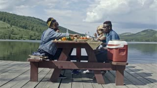 Side view of six young people sitting at table by lake, having picnic and having friendly conversation