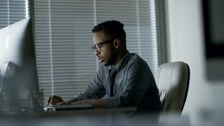 Side view of tired black man in glasses writing texts using desktop computer when sitting at desk in office