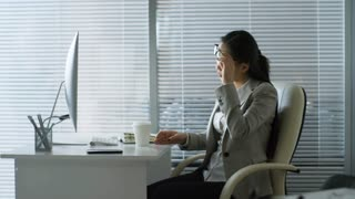 Side view of young Asian businesswoman taking off glasses and drinking takeaway coffee when working with desktop computer in office