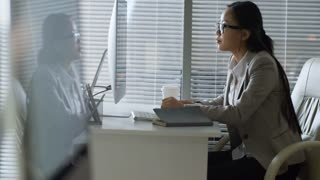 Side view of young Asian woman in glasses having video conversation with colleague or client when sitting at office desk