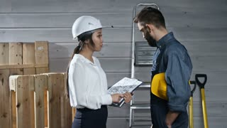 Side view of young Asian woman smiling when shaking hands with male construction worker in overalls