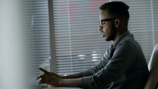 Side view of young black male employee in glasses concentrating on work when using desktop computer at office desk