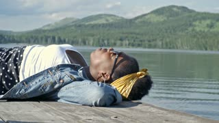 Side view of young black woman lying on wooden dock by lake, relaxing alone and looking up to the sky