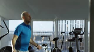 Side view tilt down shot of mature man training with jump rope at empty gym