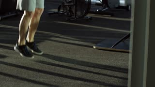 Side view tilt up shot of mature man training with jump rope at empty gym