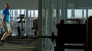 Side view tracking shot of mature man training with jump rope at empty gym