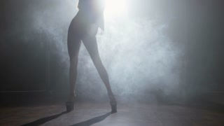 Silhouette of sensual woman in high heel shoes dancing seductively in dark foggy studio with bright spotlight in background