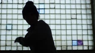 Silhouette of teenager in bobble hat dancing by opaque glass block window, medium shot
