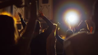 Silhouettes of multi ethnic crowd dancing with hands in the air at electronic music concert