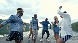 Six young friends having party outdoors, drinking and dancing in crazy way on wooden dock by lake