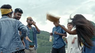 Six young friends holding drinks and dancing together in crazy and silly way at outdoor party by lake