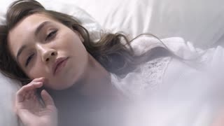 Slomo of beautiful woman in white nightgown lying in bed and looking sensualy into camera