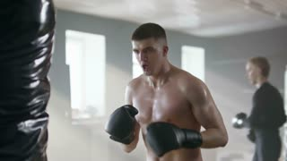Slow motion of shirtless MMA fighter in boxing gloves jumping and knee kicking punching bag