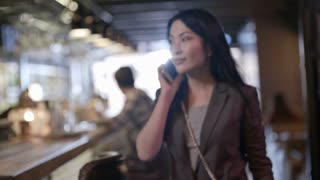 Slow motion shot of beautiful Asian woman entering restaurant while talking on mobile phone, then noticing friend off camera and waving hello