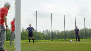 Slow motion shot of four retired male friends playing football outdoors, one kicking ball and one standing at goal net while two others are watching