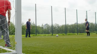 Slow motion shot of group of four active retired men playing with football on warm summer day, one of them kicking ball and one failing to catch it while standing at goal net