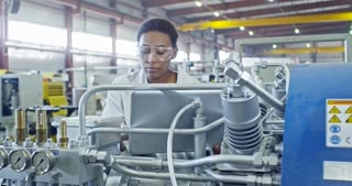 Slowmo of African female engineer in lab coat and protective eyeglasses typing on laptop while operating factory machine