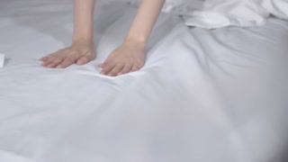 Slowmo of beautiful woman gracefully stretching on bed with white linen sheets, then looking into camera and smiling sensually