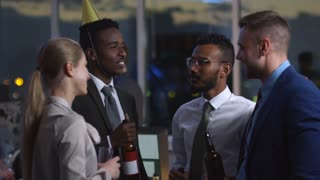 SLOWMO of multi-ethnic colleagues standing with beer and wine and discussing something at corporate party in the office at night