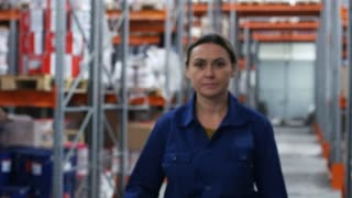 Slowmo PAN of cheerful female warehouse worker in blue uniform walking, then putting on hard hat and smiling for camera