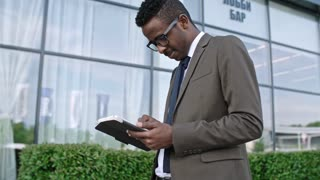 Slowmo panning shot of African businessman standing outdoors in downtown, smiling and surfing the Net on digital tablet