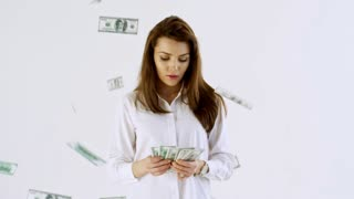 Slowmo studio shot of confident businesswoman in shirt standing isolated on white background and counting cash as money falling on her from above