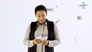 Slowmo studio shot of happy black businesswoman standing isolated on white background and counting cash as money falling down on her from above