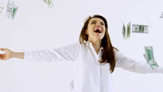 Slowmo studio shot of happy businesswoman in shirt standing with spread arms isolated on white background and laughing as money raining on her from above