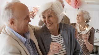Smiling elderly man and woman embracing and dancing with burning sparklers at party with friends