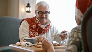 Smiling elderly man putting sweet pie on plate for his wife at restaurant table while having Christmas dinner together
