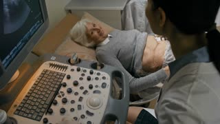 Smiling senior woman lying on medical couch, smiling and listening to doctor during ultrasound examination of stomach