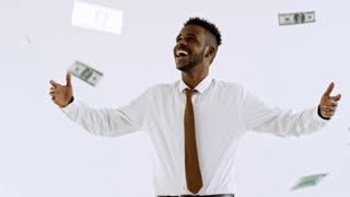 Studio shot of happy black businessman in shirt and necktie laughing and celebrating isolated on light background as heaps of money falling down on him