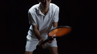 Studio shot of mature male tennis player with racquet standing in ready position isolated on black background