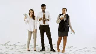Studio shot of multi-ethnic carefree businesspeople with stacks of money standing isolated on white background and throwing cash in air