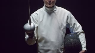 Studio shot of young professional fencer in white costume moving sword towards the camera and putting protective mask