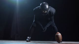 Studio shot with black background of American football player in full uniform and helmet leaning and looking at ball spinning on floor