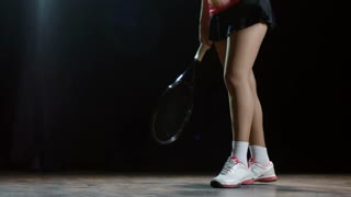 Studio shot with low-section of unrecognizable female tennis player with racquet standing against black background and bouncing ball on floor while preparing to hit serve