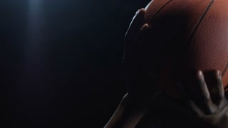 Studio shot with slowmo of unrecognizable basketball player throwing ball against dark background
