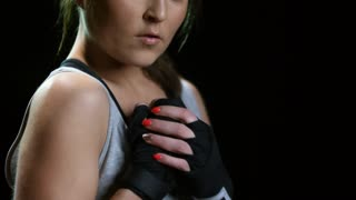 Studio shot with tilt up of focused female fighter looking at camera and cracking knuckles isolated on black background