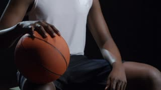 Studio shot with tilt up of smiling black basketball player with ball sitting isolated on dark background and posing for camera