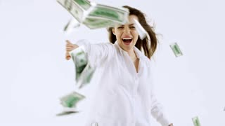 Studio shot with white background: ecstatic woman in white shirt laughing and flailing her arms as cash money flying towards her