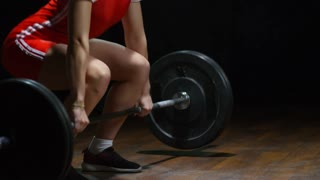 Studio with tilt up of focused young female weightlifter in sportswear doing clean and jerk lift with barbell against black background