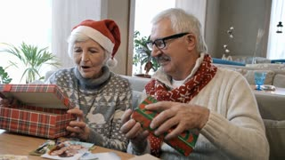 Surprised senior man and woman in Santa hat sitting on couch at restaurant table and opening Christmas gifts at holiday dinner