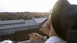 Tattooed man in eyeglasses and hat sitting on rooftop, looking up at the sky and enjoying view of Bali town on vacation