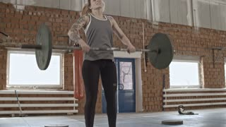 Tattooed sweaty woman squatting with barbell on shoulders and doing lunges during intensive workout in cross-training gym