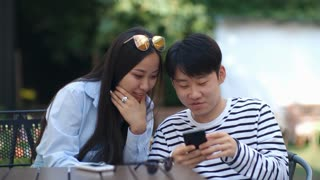 Teen Asian boy and girl watching something in the Internet on smartphone, talking and laughing while sitting at cafe table outdoors