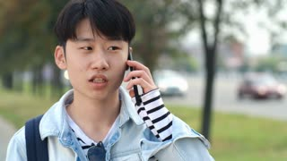 Teen Asian boy standing on the street at summer day and talking on mobile phone