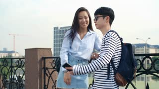 Teenage Asian boy and girl in trendy outfits standing at riverside in the city at summer day and taking selfie with smartphone