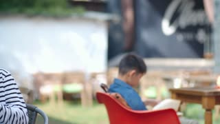 Teenage Asian boy and girl sitting together at table in outdoor cafe at summer day, taking selfie with smartphone, smiling and looking at picture
