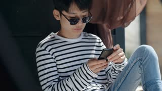 Teenage Asian boy in eyeglasses sitting on outdoor terrace and surfing the Internet on smartphone